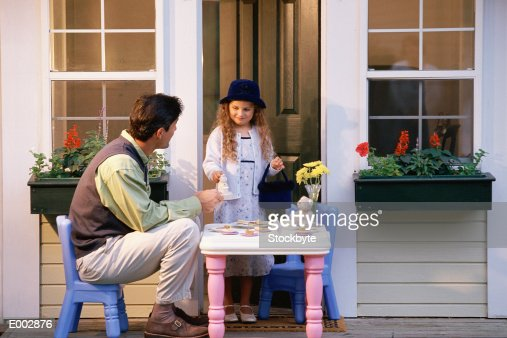 Girl having tea party with her father