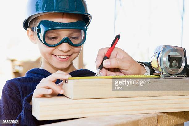 Girl helping father measure wood plank