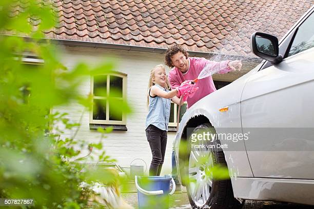 Girl helping father wash his car