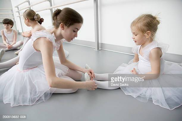 Girl (10-12) helping girl (2-4) put on shoes in ballet class