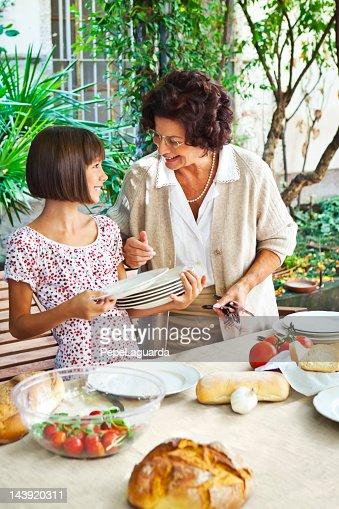Girl helping grandmother setting table
