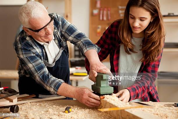 Filles aidant à atelier de menuiserie grand-papa