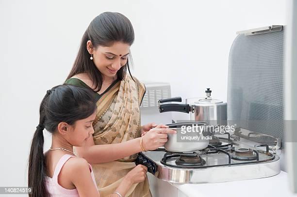 Girl helping her mother in preparing food