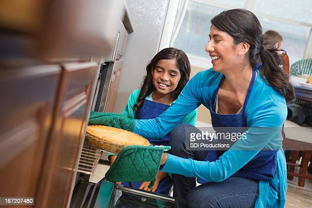 Girl helping mom take pie from oven in family kitchen