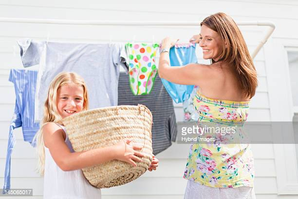Girl helping mother hang laundry