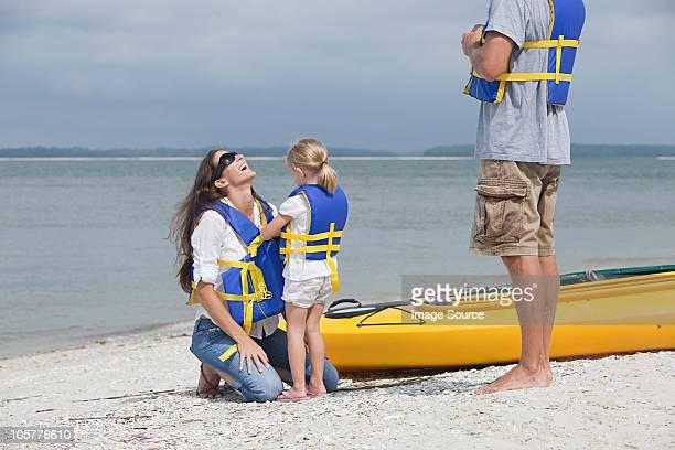 Girl helping mother put on lifejacket for kayaking