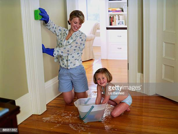 Girl helping mother scrub walls
