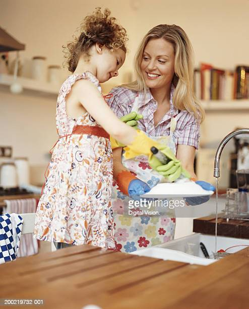 Girl (4-6) helping mother wash-up, smiling