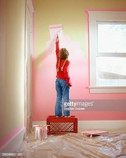 Girl (4-6) helping to paint bedroom, rear view