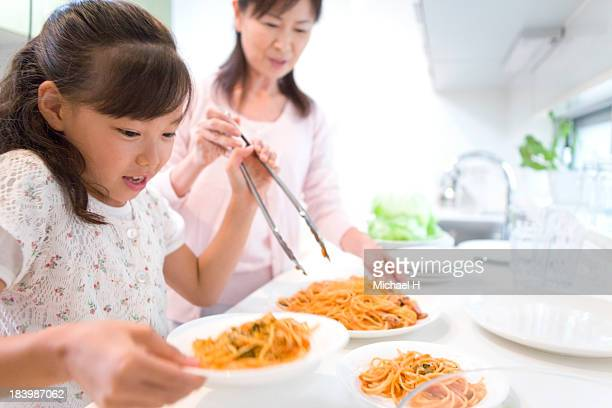 A girl helps grandma's cooking in the kichen