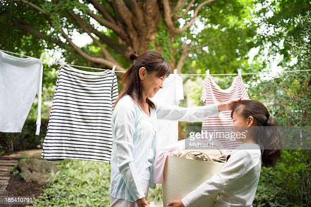 A girl helps grandma's laundry in the garden