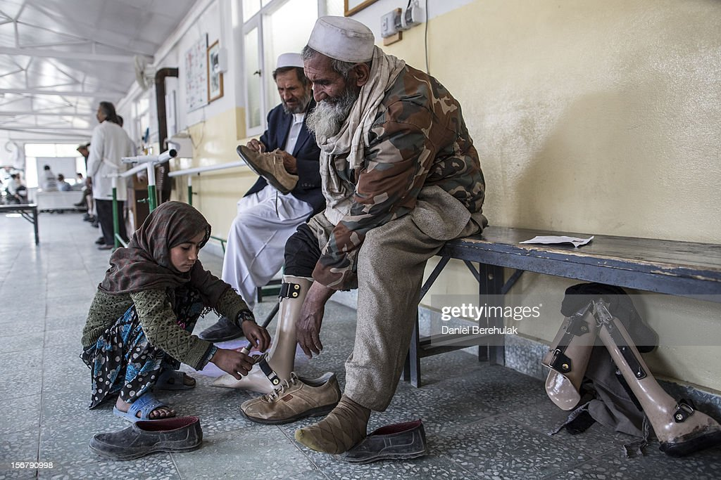 A girl helps her father put on his leg braces at the International Committee of the Red Cross (ICRC), orthopedic centre on November 20, 2012 in Kabul, Afghanistan. The ICRC rehabilitation centre works to educate and rehabilitate land-mine victims, and those with limb related deformities, back into society and employment offering micro-credit financing, home schooling and vocational training to patients. The clinic itself is unique in that all of the workers are handicapped. The ICRC centre in Kabul has registered over 57,000 patients and 114,000 countrywide in all of their centres since its inception 25 years ago.
