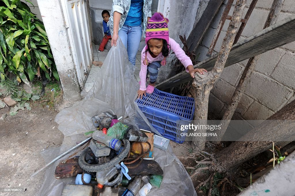 A girl helps her mother in the fight against Aedes Aegypti mosquito that transmits Zika virus, as well as viral diseases such as dengue and chikungunya, in Tegucigalpa on February 6, 2016. Honduras on Mondayy declared a state of emergency after officials said the number of Zika infections was rising at an 'alarming' rate in the Central American country. Since December 16, when the first case of the mosquito-borne virus was detected, there have been more that 4,000 cases of people infected with the virus in Honduras. AFP PHOTO / ORLANDO SIERRA / AFP / ORLANDO SIERRA
