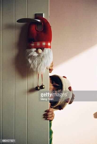 Girl hide behind the door on Christmas eve
