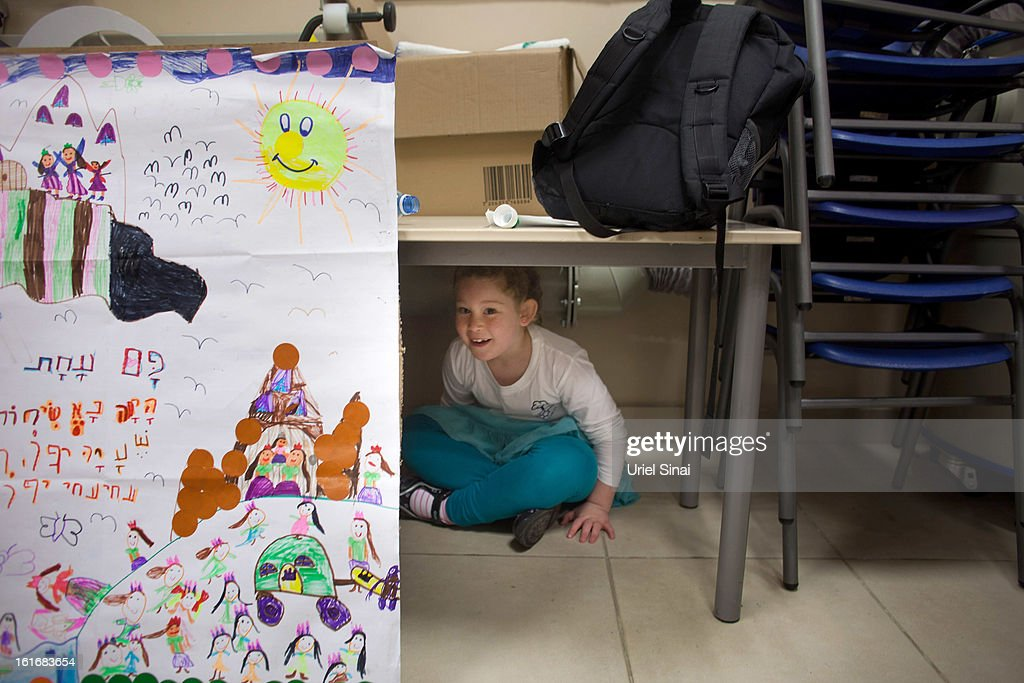 A girl hides under a table as Israeli schoolchildren take cover in a bomb shelter during a Home Front command drill simulating a rocket hitting a school on February 14, 2013 in Ra'anana, Israel. Working with the schools and emergency services, local authorities want to increase readiness for possible future attacks.