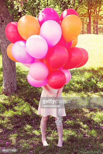 Girl hiding behind a pink balloon bouquet in spring nature.