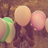 Girl hiding behind balloons