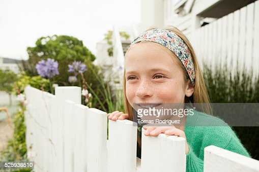 Girl (8-9) hiding behind fence : ストックフォト