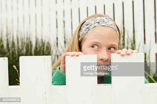 Girl (8-9) hiding behind fence : Stockfoto
