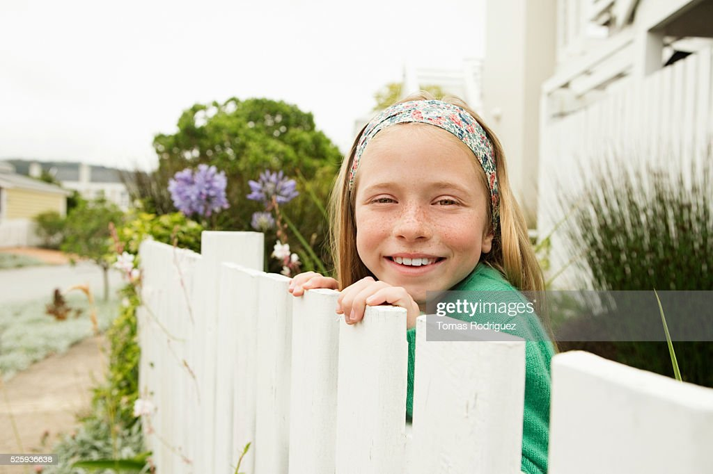 Girl(8-9) hiding behind fence : Stockfoto