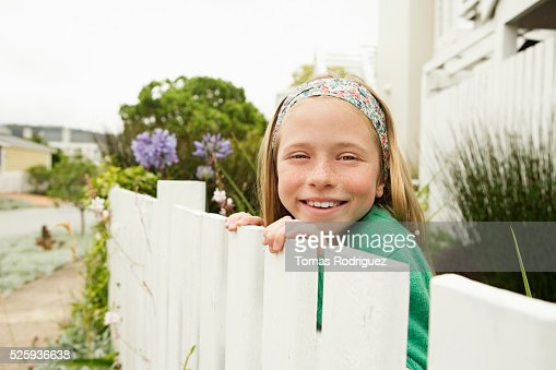 Girl(8-9) hiding behind fence : Stock Photo