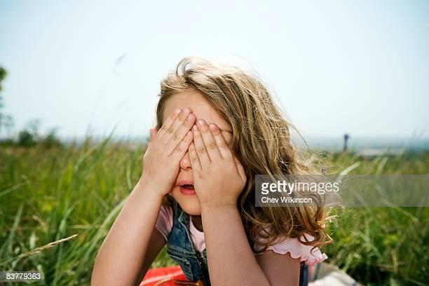 Girl hiding behind hands