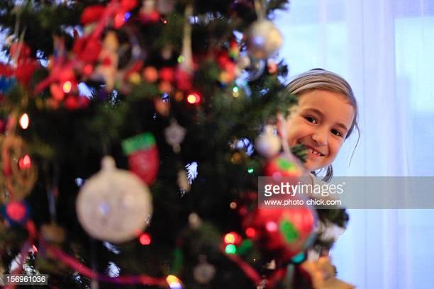 A girl hiding behind the christmas tree