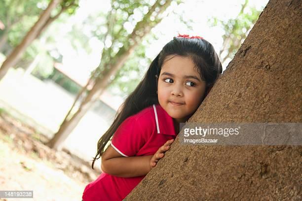 Girl (4-5) hiding behind tree