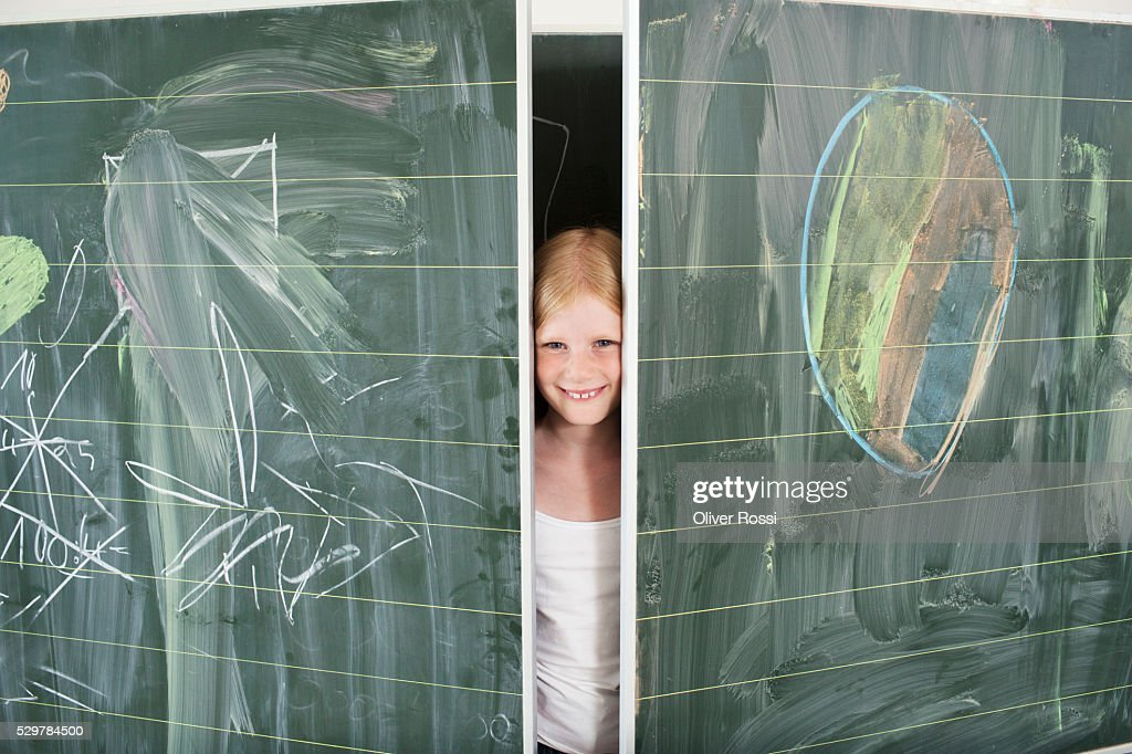 Girl hiding between blackboards : Stock Photo