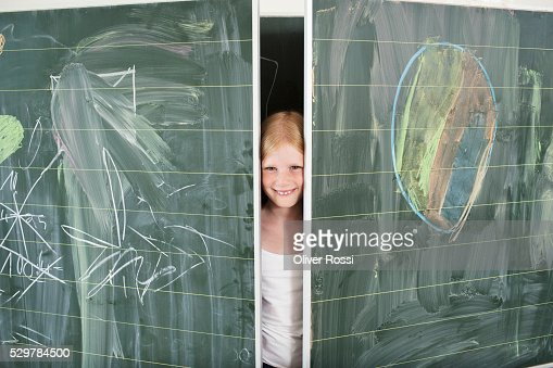 Girl hiding between blackboards : Stock-Foto
