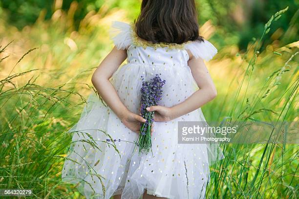 Girl hiding bouquet of lavender behind