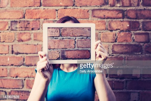 Girl hiding her face with tablet : Stock Photo
