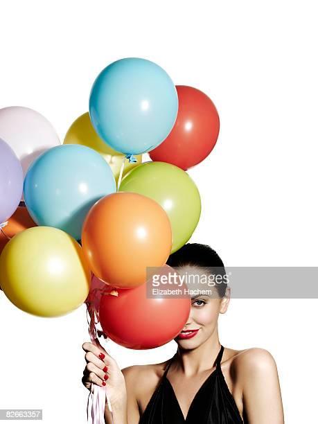 Girl hiding one eye behind a bunch of balloons