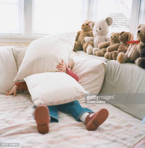 Girl Hiding under Pillows