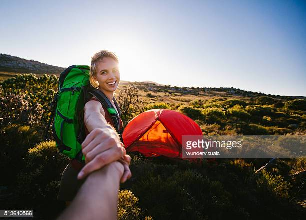 Girl hiker leading her boyfriend by holding hands to tent