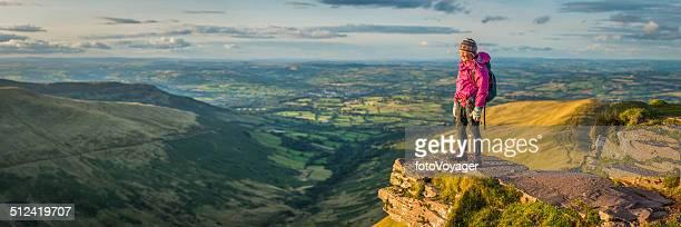 Girl hiker on idyllic mountain ridge looking at panoramic vista
