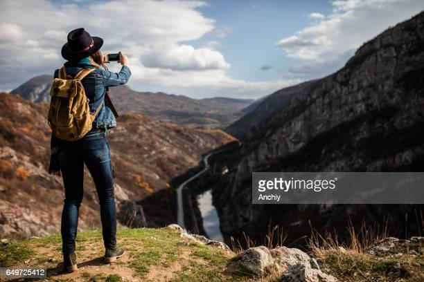 Girl hiker on top of the cliff taking photo of a gorge, depth of field