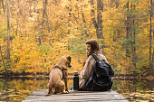 Young female person and her staffordshire terrier puppy having a rest by the lake on beautiful october day of indian summer