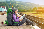 Happy girl tourist with backpack sits on a platform waiting for a train. Travel concept. Traveler holding map, waiting for a train and planing for next trip. Traveler reading map