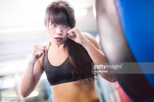 Girl Hitting a Punching Bag