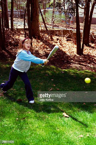 Girl hitting baseball