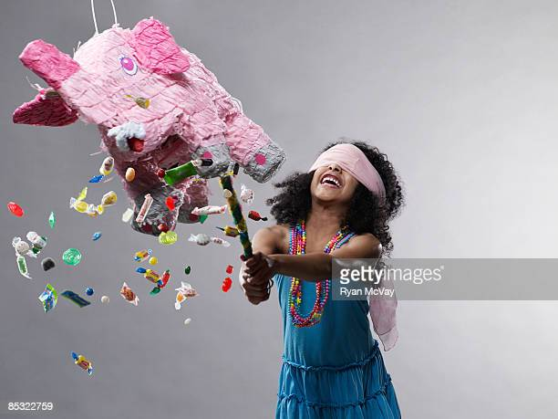 Girl hitting pinata, candy flying