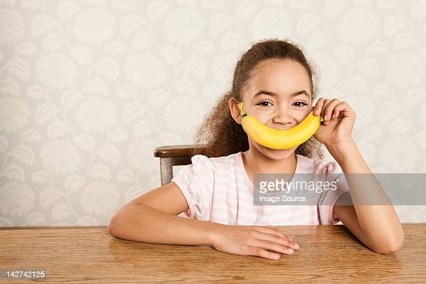 Girl holding a banana over her mouth