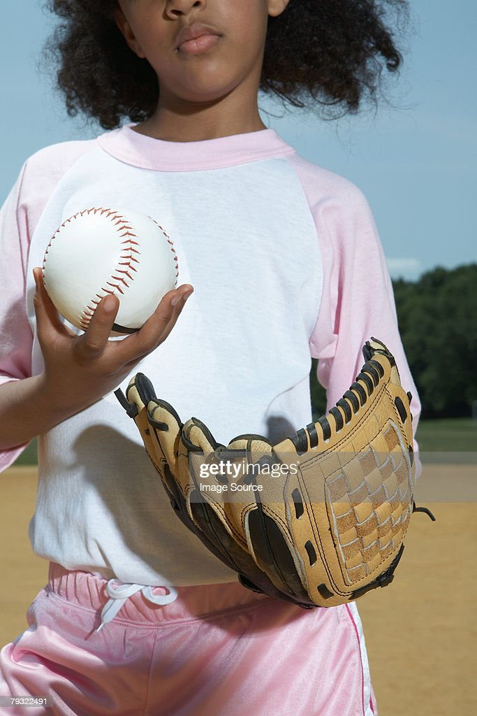 A girl holding a baseball and baseball glove