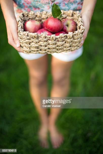 Girl holding a basket full of apples