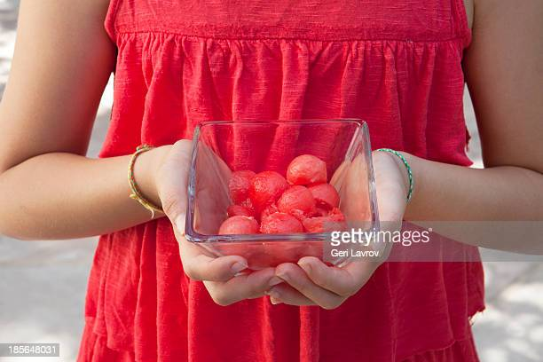Girl holding a bowl of watermelon scoops