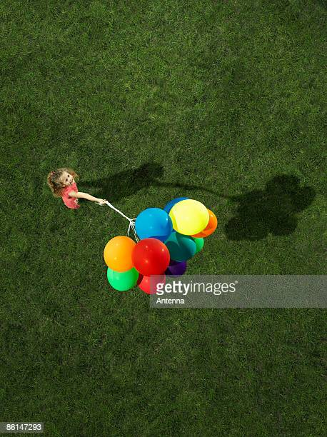 A girl holding a bunch of helium balloons