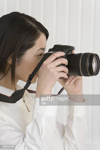 Girl holding a camera and photographing, side view
