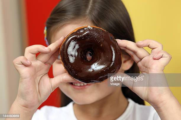 Girl holding a chocolate doughnut
