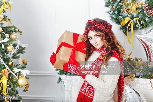 Girl holding a Christmas present. : Stock Photo